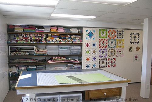DIY sliding design wall in my quilt studio with quilt blocks on it
