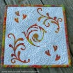 Mini batik quilt with a penny on it
