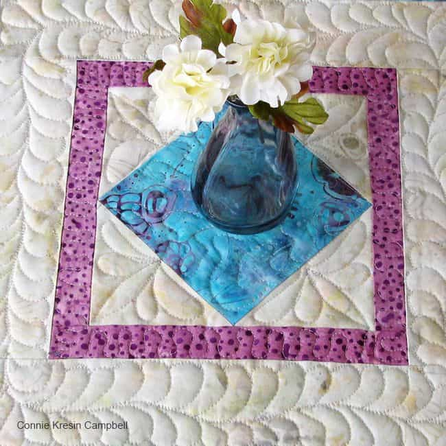 Square in a square table topper quilting closeup