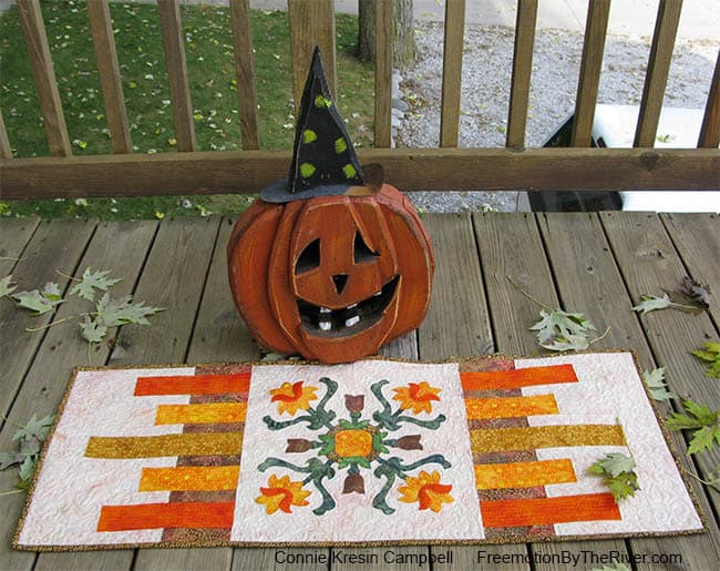 Folk Art Quilted Tradtions applique table runner with a Halloween pumpkin