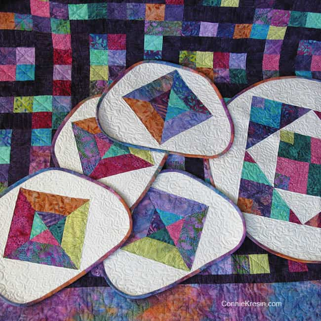 Quilted Batik Placemats and table topper on quilt
